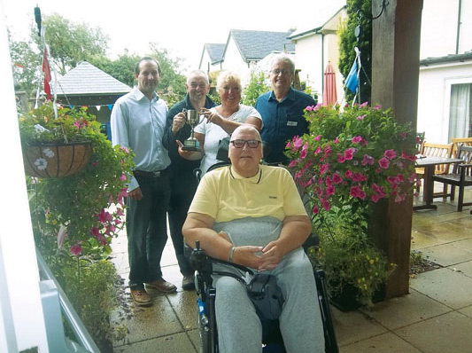 Belmore Lodge staff and residents celebrate winning this year's garden competition. The home has an active residents' garden club and even staff meetings are held outdoors whenever possible.