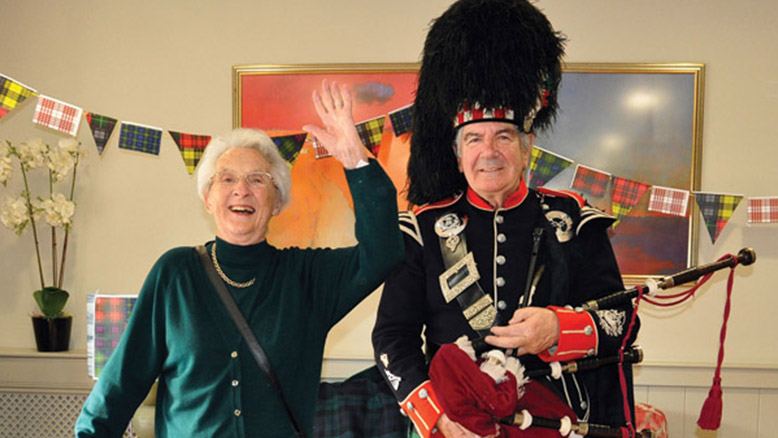 Avon Reach resident Betty Butler with visiting piper John Adams on Burns' Night this year