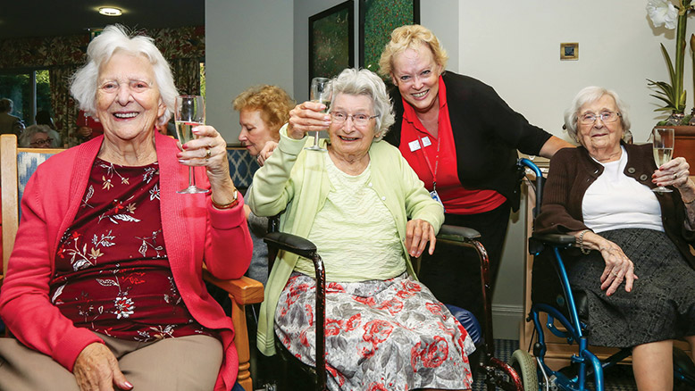 CHEERS: Residents and staff raise a glass of champagne to Canford Chase's success at a special celebration party