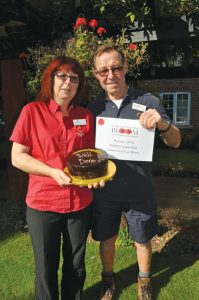 Amberwood House gardener Peter Burns is presented with a congratulatory cake for the home's Ferndown in Bloom success by Activity Organiser Jan Burns (no relation).