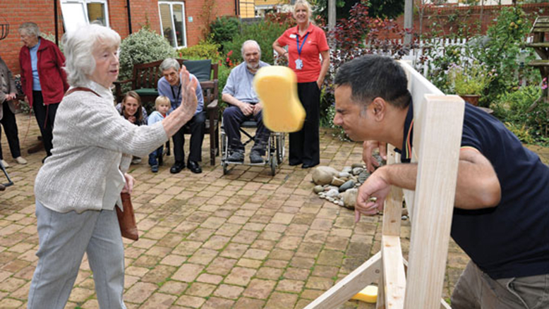 TAKE THAT: Catherine Matthews, a resident at Newstone House, enjoys the wet sponge challenge with Home Manager Sohail Daniel