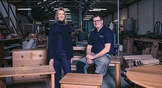 Georgina Colwell, our Head of Design, and Alan Webber, Managing Director of Webber Furniture. Around them are handcrafted oak tables and drawer units for Bourne View.