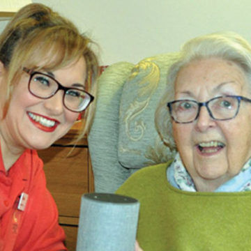 Norma Richards of Newstone House is one of many residents benefitting from the use of technology at the home. Norma is seen here with her smart speaker which she uses to play music she performed to during her career as a ballet dancer.