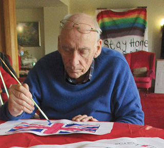 Resident Rob at Castle View in Dorchester finishing off VE Day flags for the commemoration.