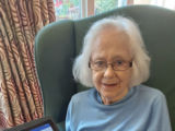 Newstone House resident Rosemary Cottrell with the new tablet donated by AJ Bell