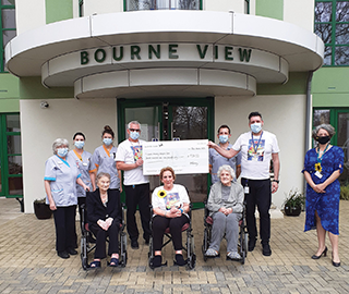 SO PROUD: Molly is joined by staff and fellow residents at Bourne View where she completed a 100-mile static cycling challenge in aid of Lewis-Manning Hospice Care.