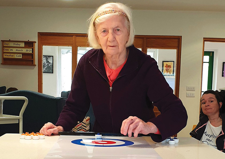 Diana Janes playing shuffleboard at The Aldbury. Watching is fellow resident Pip Smith.