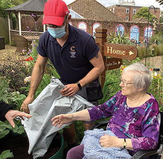 Gardener Chris Marsh adds extra soil for the potatoes, working with residents at Linden House to help with an entry for the Colten Annual Village Produce Show.